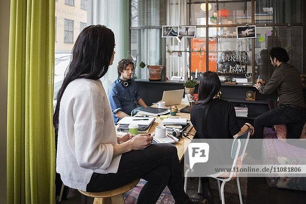 Kreatives Team beim Betrachten des Schreibens in Haftnotiz im modernen Büro
