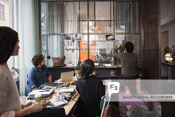 Kollegen beim Anblick eines Mannes  der im Kreativbüro Haftnotizen auf Glas klebt.