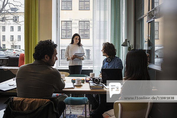 Geschäftsfrau im Gespräch mit Kreativen im modernen Büro