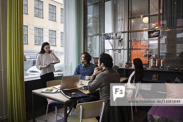 Kreative Geschäftsfrau im Austausch mit dem Team im modernen Büro