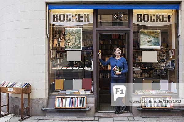 Bibliothekarin hält Buch  während sie auf den Eingang blickt