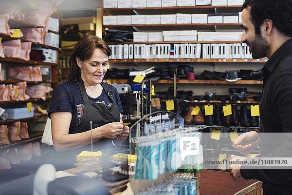 Lächelnder Kunde betrachtet Schuhmacher beim Lesen des Namensschildes im Geschäft