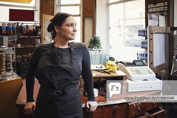 Lächelnde Kassiererin im Stehen beim Wegschauen in der Werkstatt