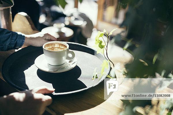 Abgeschnittenes Bild der Hände  die das Serviertablett mit Kaffeetasse im Café halten.