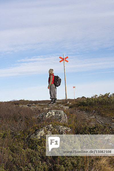 Woman hiker standing near trail sign