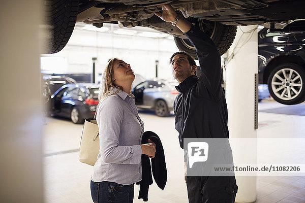 Experte mit Kunde unter dem Auto in der Werkstatt