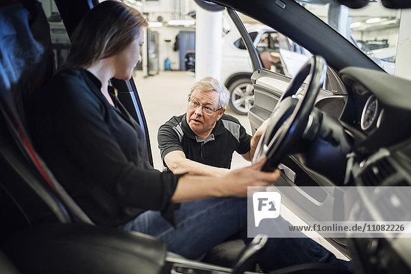 Senior-Expertin im Gespräch mit Kundin im Auto in der Werkstatt