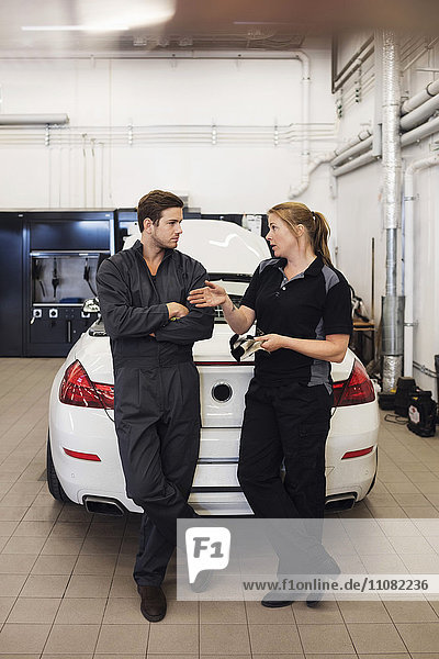 Full length of mechanics discussing while standing against car in shop