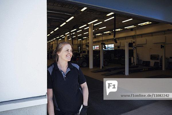 Lächelnde Mechanikerin schaut weg  während sie sich in der Werkstatt an die Wand lehnt.