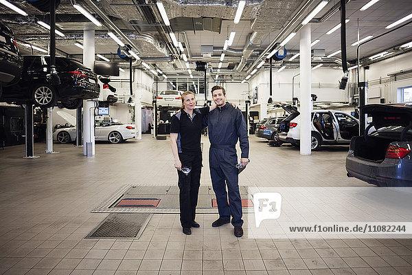Portrait von glücklichen Experten  die in der Autowerkstatt herumstehen