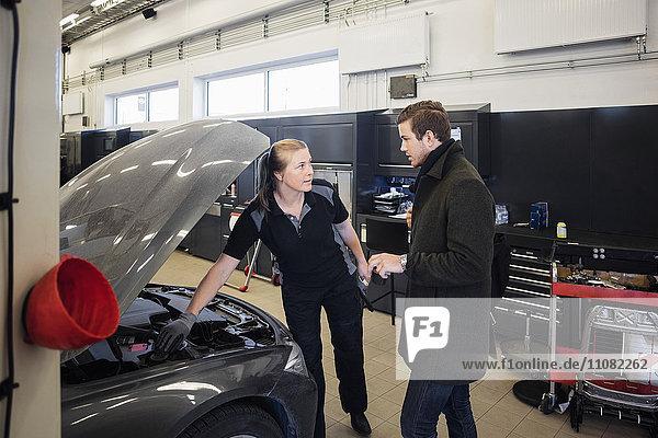 Kundengespräch mit Kfz-Mechanikerin in der Autowerkstatt