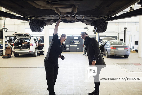 Female expert and client standing under car at repair shop