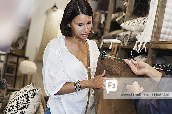 Beschnittenes Bild des Besitzers mit braunem Rock für die Kundin im Geschäft