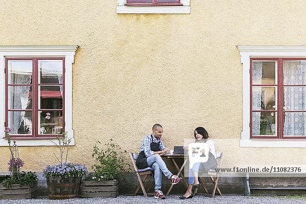 Mann und Frau diskutieren über das digitale Tablett  während sie am Tisch vor dem Café sitzen.
