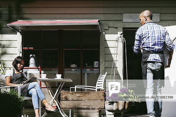 Mann geht in Richtung Café und schaut auf eine Kollegin  die an einem digitalen Tablett arbeitet.