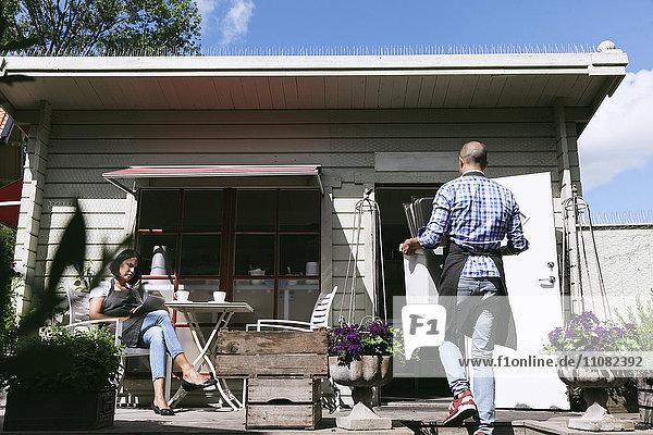 Mann mit Serviertabletts beim Spaziergang durch die Frau  die am Tisch vor dem Café arbeitet.