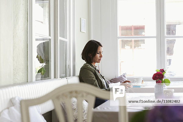 Seitenansicht der Frau beim Telefonieren und Kaffeetrinken im Cafe