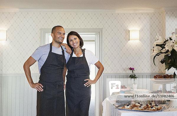 Lächelnde Besitzer stehen beim Dessert am Tisch im Cafe