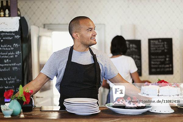 Lächelnder männlicher Besitzer steht am Cafe Tresen mit Mitarbeiter im Hintergrund