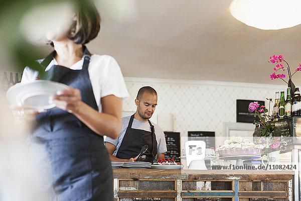 Frau hält den Teller und geht gegen einen männlichen Kollegen  der an der Cafeteria arbeitet.