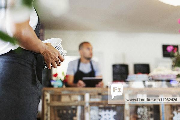 Frau hält Tellerstapel  während Mitarbeiterin am Kaffeetresen steht
