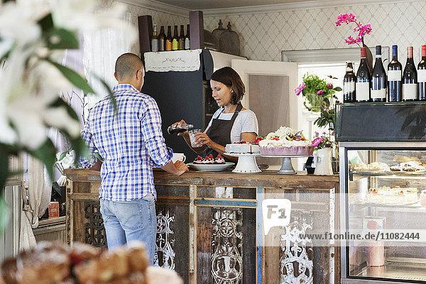Besitzerin serviert Getränk im Glas für Kunden an der Theke im Cafe