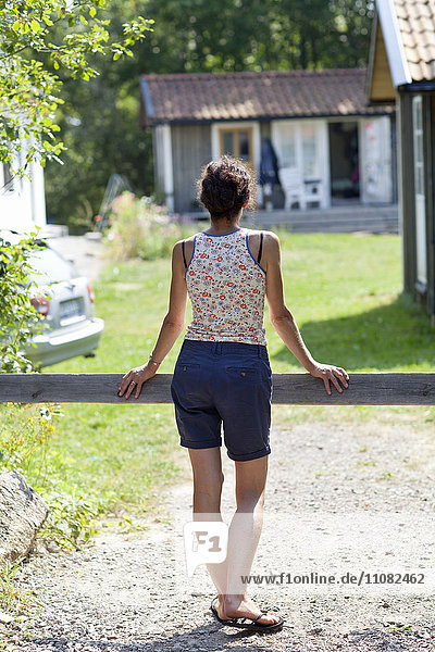 Rear view of woman looking at house