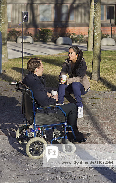 Young woman and man on wheelchair having coffee break