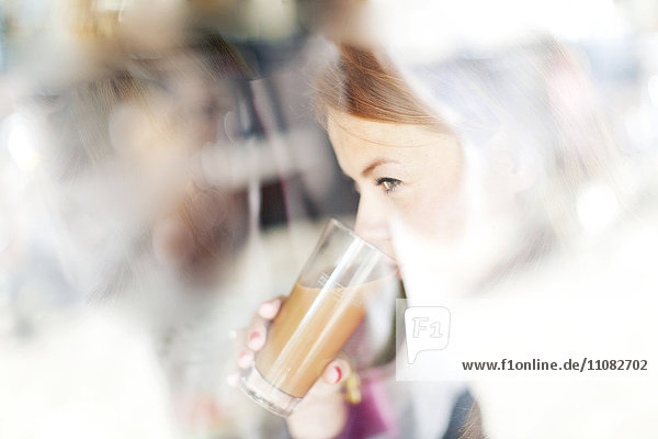 Woman drinking latte in cafe
