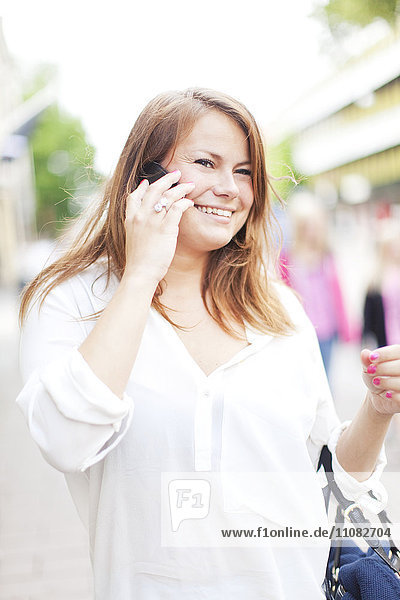 Smiling young woman talking via cell phone  Vaxjo  Smaland  Sweden