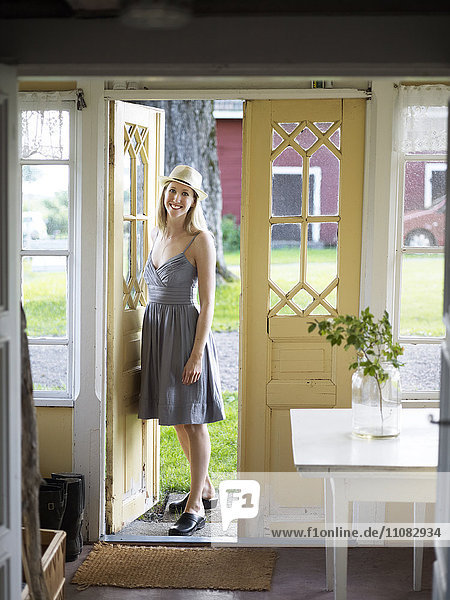 Smiling woman standing at doorway