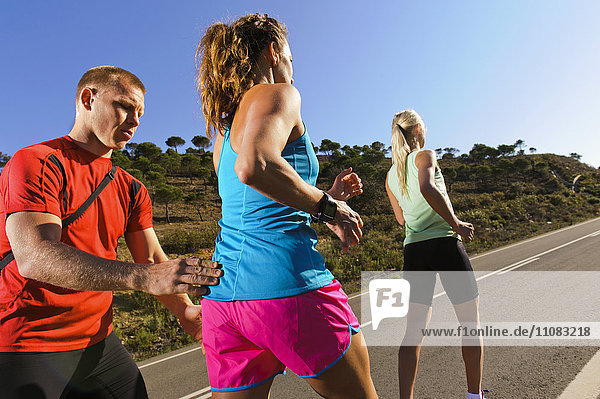 Trainer and women jogging on road