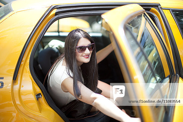 Smiling young woman in yellow taxi  New York City  USA