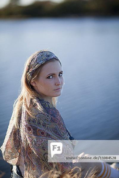 Young woman at water looking at camera