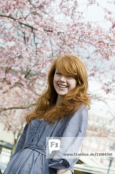 Young woman with blossom in cherry trees around