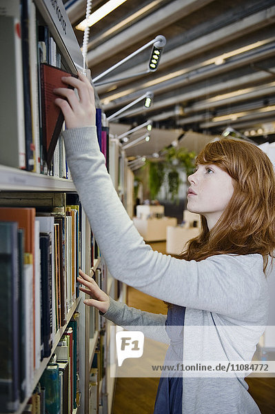 Young woman choosing book in library