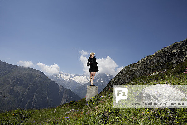 Blond woman wearing a black dress in mountain scenery  Switzerland.