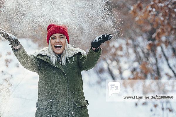 Porträt einer fröhlichen jungen Frau beim Spielen im Schnee