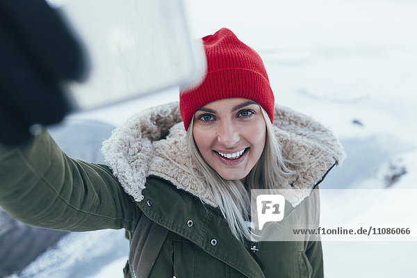 Smiling young woman taking selfie on smart phone during winter