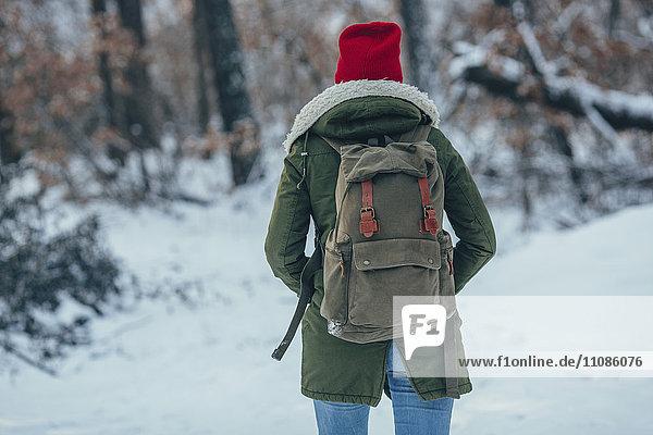Rückansicht einer jungen Frau mit Rucksack auf schneebedecktem Feld