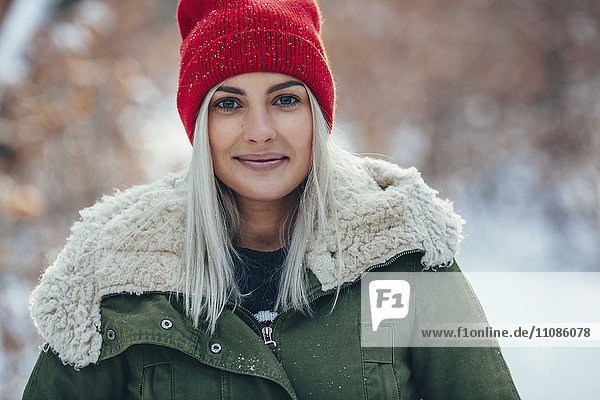 Portrait of confident young woman standing outdoors during winter