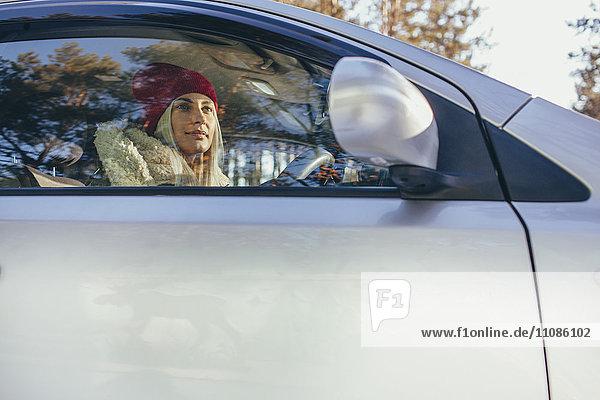 Niederwinkelansicht der Frau  die im Winter Auto fährt.