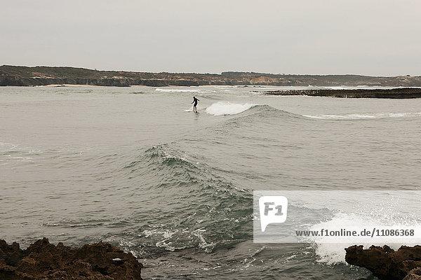Person beim Surfen am Strand  Vila Nova de Milfontes  Portugal