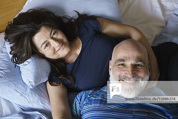 High angle view of mature couple lying on bed at home