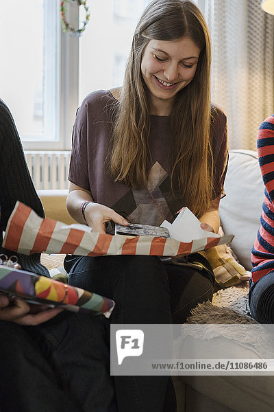 Junge Frau  die zu Hause ein Geschenk macht