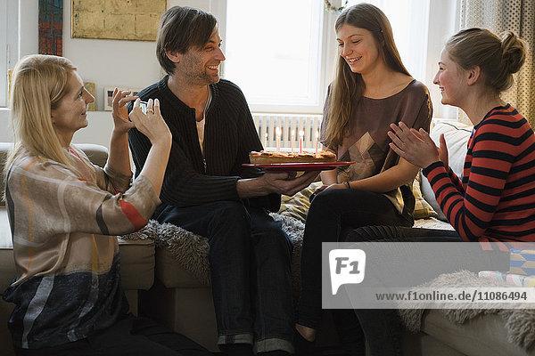 Glückliche Frau schaut auf die Familie mit Geburtstagskuchen im Wohnzimmer