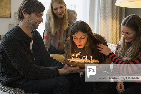 Familie betrachtet junge Frau beim Ausblasen von Geburtstagskerzen zu Hause