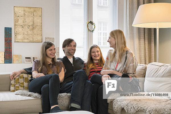 Eine glückliche vierköpfige Familie  die zu Hause auf dem Sofa sitzt.
