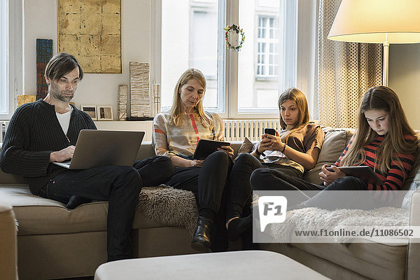 Eltern und Töchter mit Laptop und mobilen Geräten auf dem Sofa im Wohnzimmer