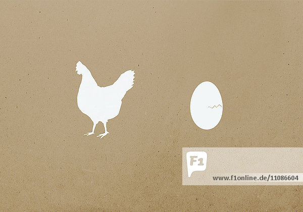 Hen and egg against brown background